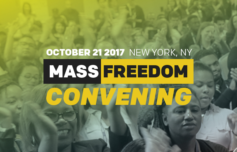 Text: October 21 2017. New York, NY. Mass Freedom Convening. Background: Crowd of people with hands raised.